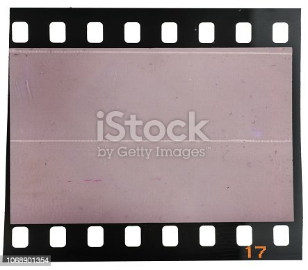 1129542015 istock photo Real macro photo of old and vintage looking 35mm film strip or dia frame on white 1068901354