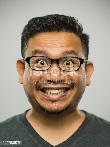 Close up portrait of asian man with very excited expression against white gray background. Vertical shot of malaysian real people surprised in studio with black hair and glasses. Photography from a DSLR camera. Sharp focus on eyes.