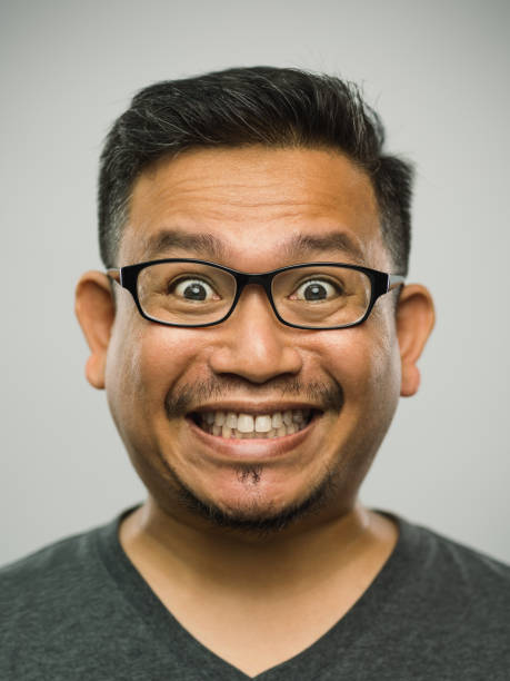 Real malaysian adult man with very excited expression Close up portrait of asian man with very excited expression against white gray background. Vertical shot of malaysian real people surprised in studio with black hair and glasses. Photography from a DSLR camera. Sharp focus on eyes. grimacing stock pictures, royalty-free photos & images