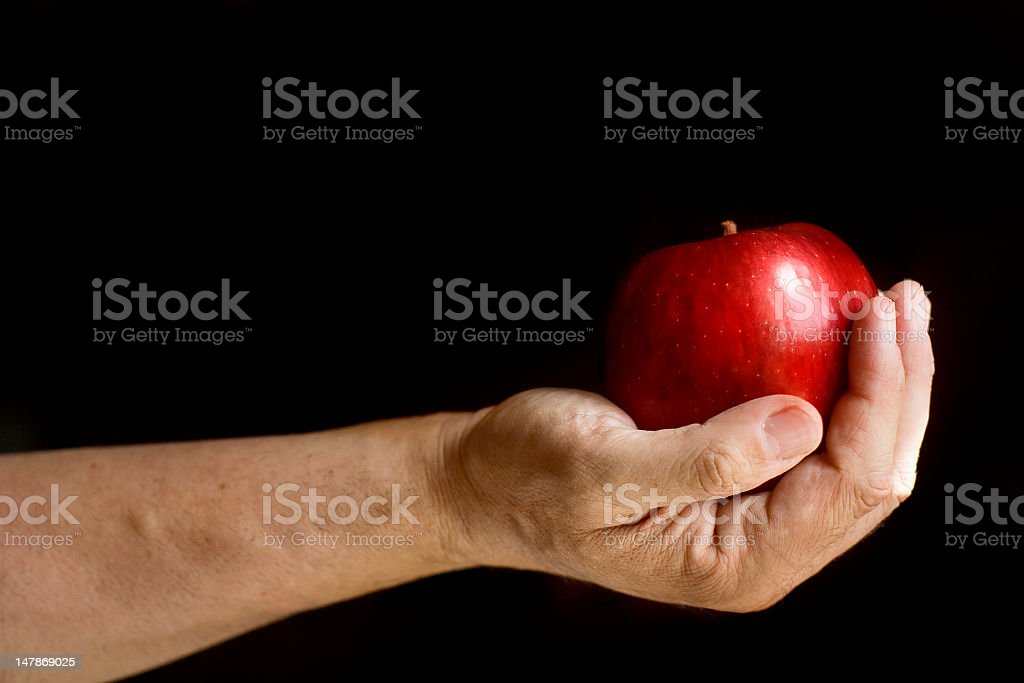 Real Man Hand Offering a Red Apple stock photo