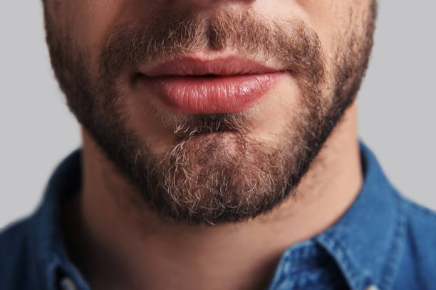 Real man. Close up of young unshaved man standing against grey background mouth stock pictures, royalty-free photos & images