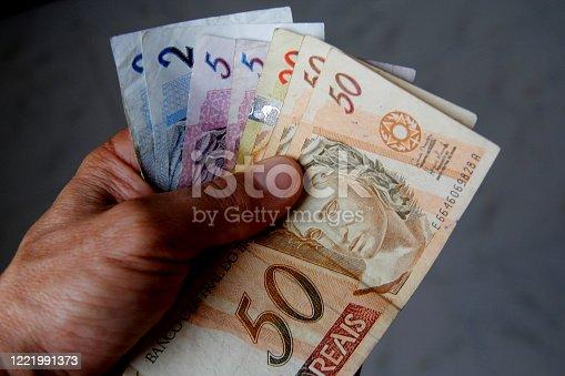 salvador, bahia / brazil - january 19, 2013: Hand hold Brazilian Real currency notes..