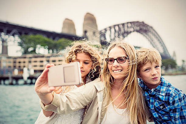 Real mother taking selfie with her kids, Sydney Harbour Bridge stock photo