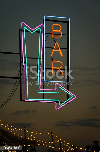 istock Real neon bar sign and arrow during dawn in a summer festival 1162625541