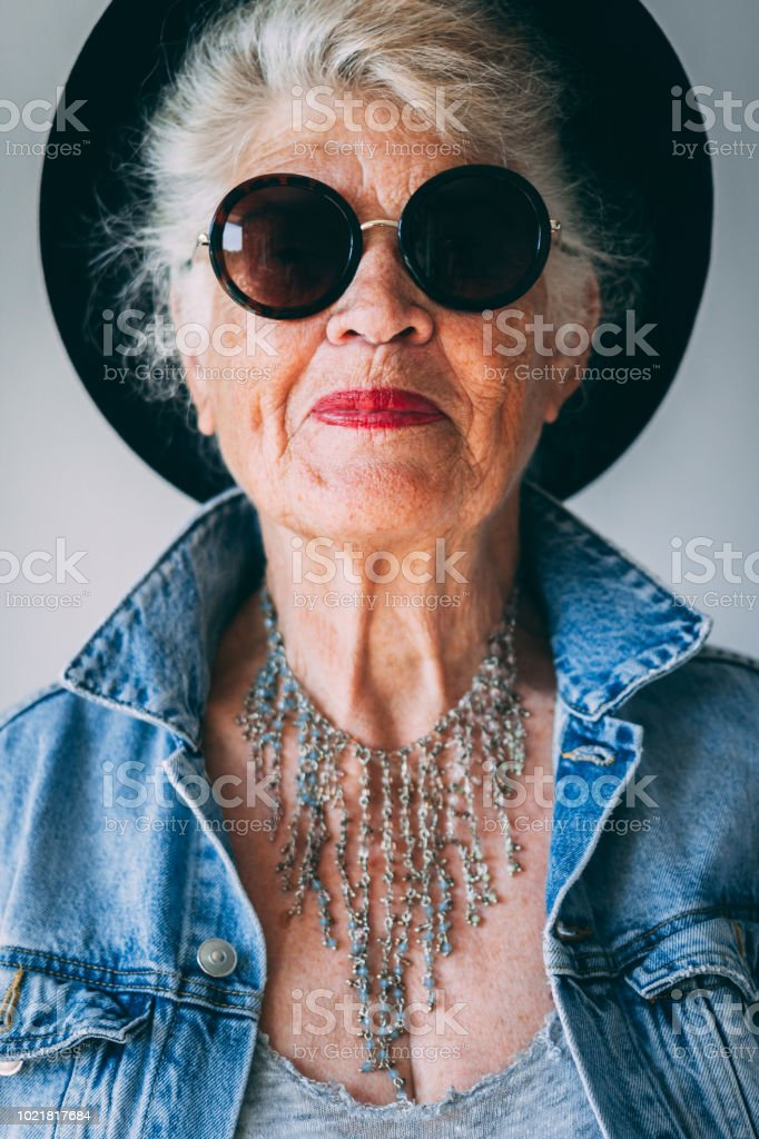 Elderly woman dressed as hipster takes selfie with mobile phone...