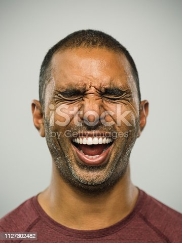 Close up portrait of adult middle eastern man with excited expression and eyes closed against white gray background. Vertical shot of real people from Pakistan laughing with exhilaration in studio with short black hair. Photography from a DSLR camera. Sharp focus on eyes.
