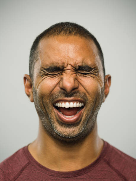 Real pakistani man with excited expression and eyes closed Close up portrait of adult middle eastern man with excited expression and eyes closed against white gray background. Vertical shot of real people from Pakistan laughing with exhilaration in studio with short black hair. Photography from a DSLR camera. Sharp focus on eyes. grimacing stock pictures, royalty-free photos & images
