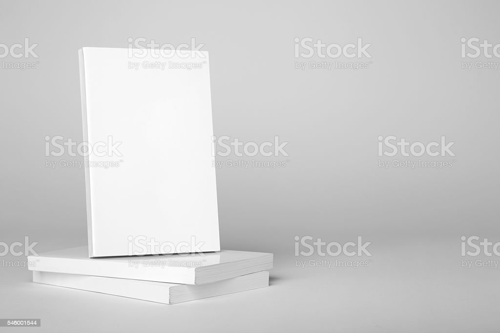 Real paperback white book over a stack of books stock photo