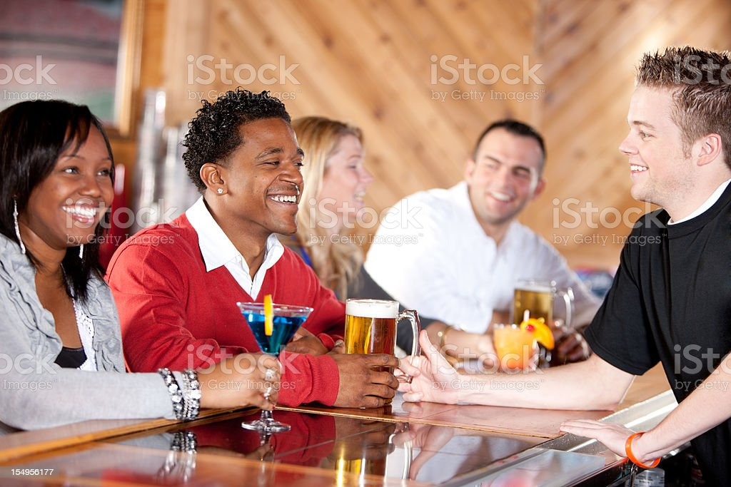 Real People: Adult Couples Bartender at Bar Caucasian African American royalty-free stock photo