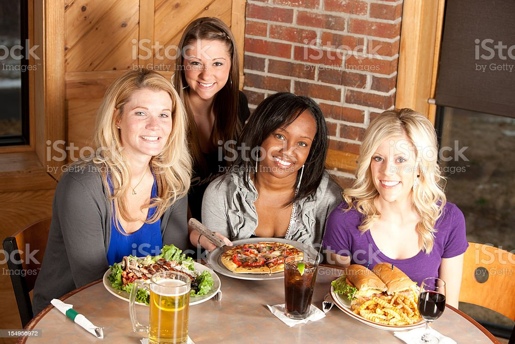 Real People: Adult Women Friends Eating at Restaurant Head Shoulders royalty-free stock photo