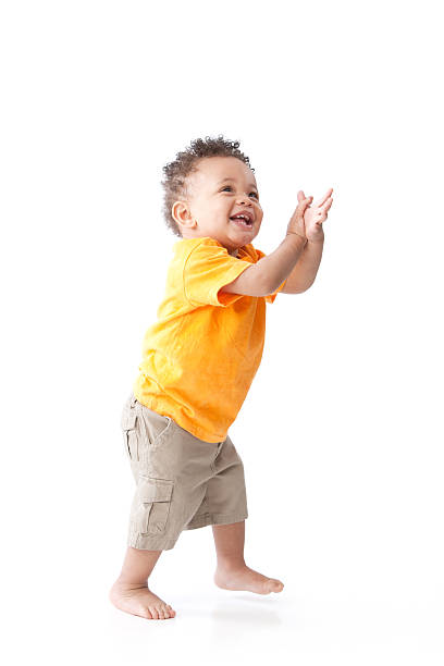 Real People: Black Laughing Toddler Boy Orange Standing Clapping stock photo