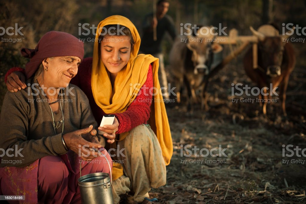 Happy peasant girl showing mobile phone to her grandmother and her...