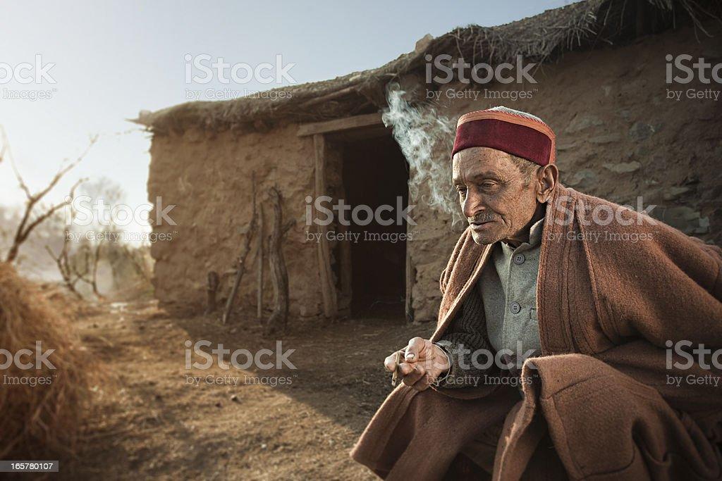 Real people from rural India: Senior man smoking Bidi royalty-free stock photo