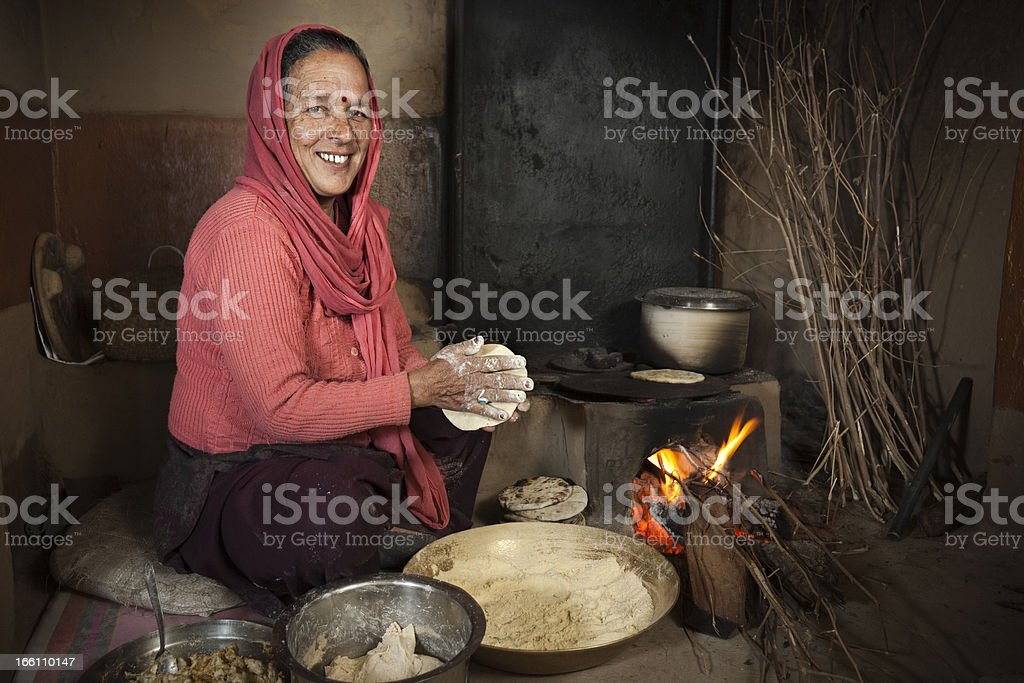 Real people from rural India: Senior woman cooking traditional food. stock photo