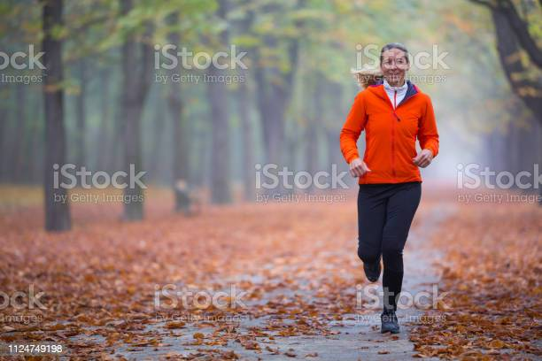 Photo of real people happy woman running alone in park on misty autumn morning