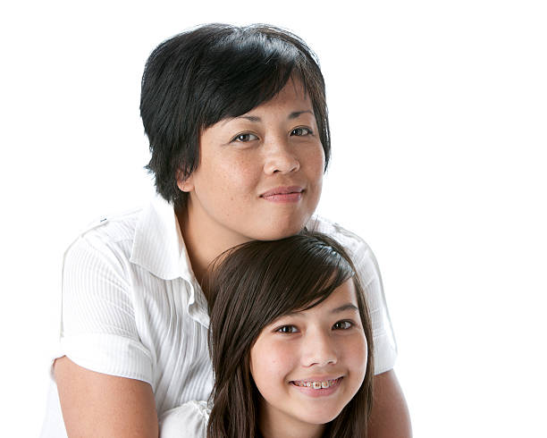 Real People: Head Shoulders Smiling Asian Mother and Teenage Daughter stock photo