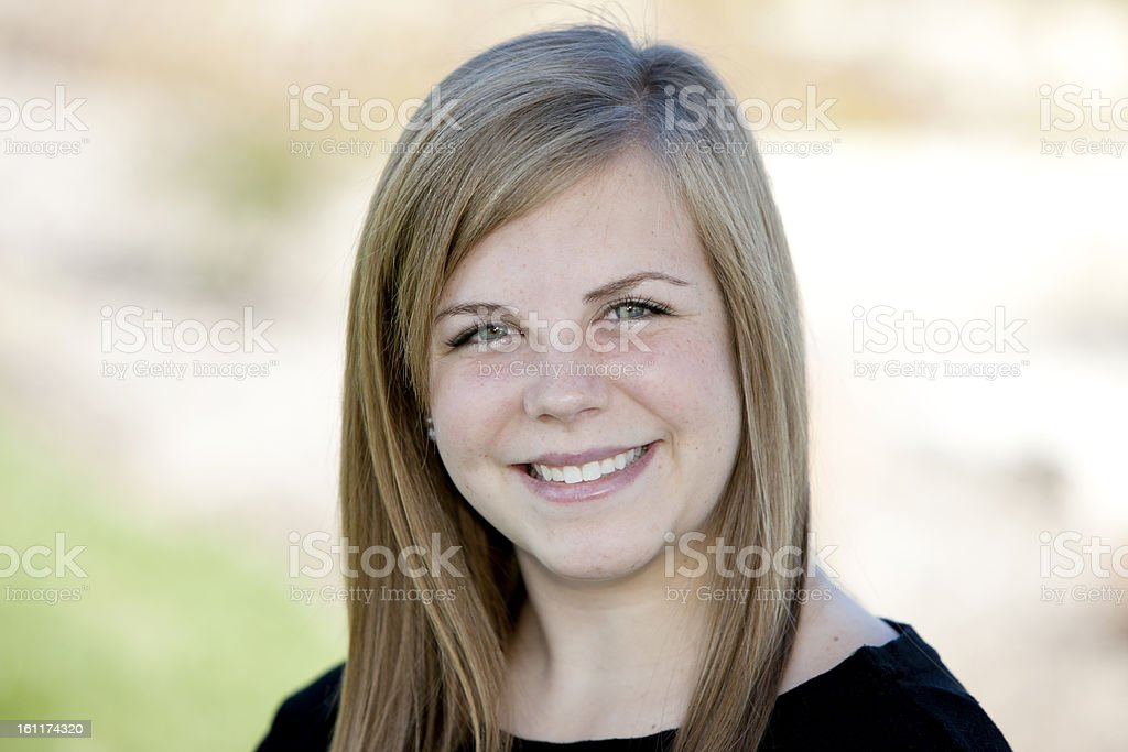 A head and shoulders image of a smiling caucasian real teenage girl....