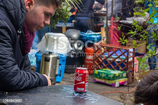 A Caucasian man sits at a table in Camden market with a can of Coca-Cola in front of him