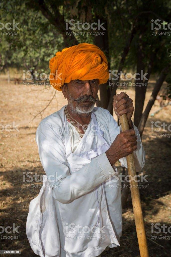 a senior person wearing traditional dress with farm tool in rajasthan