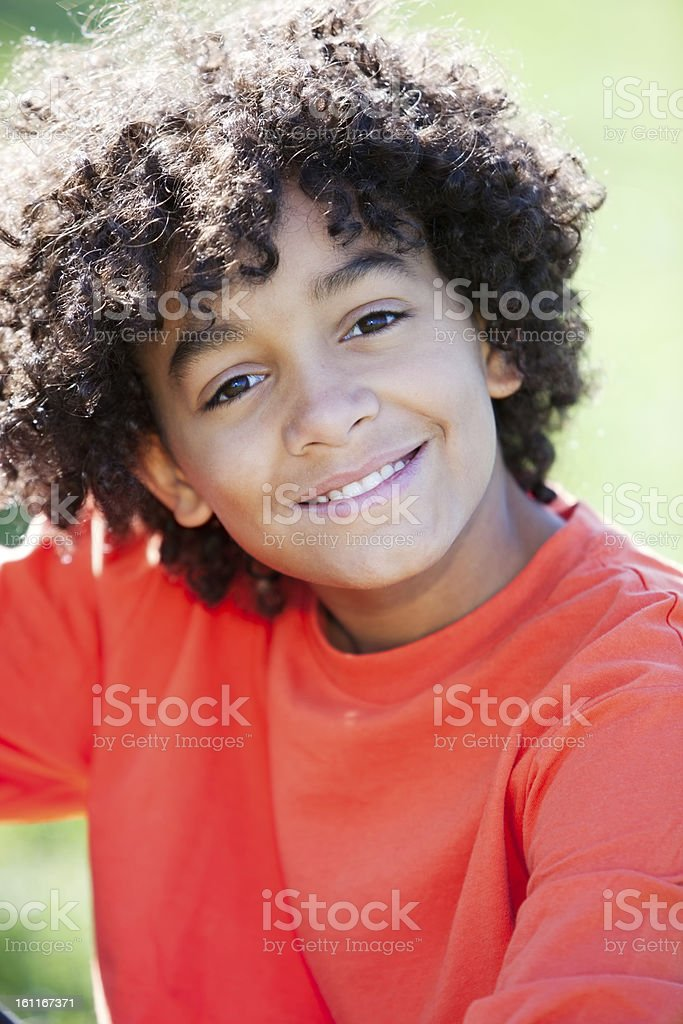 Real People: Mixed Race Boy Sitting in Park Closeup Headshot royalty-free stock photo