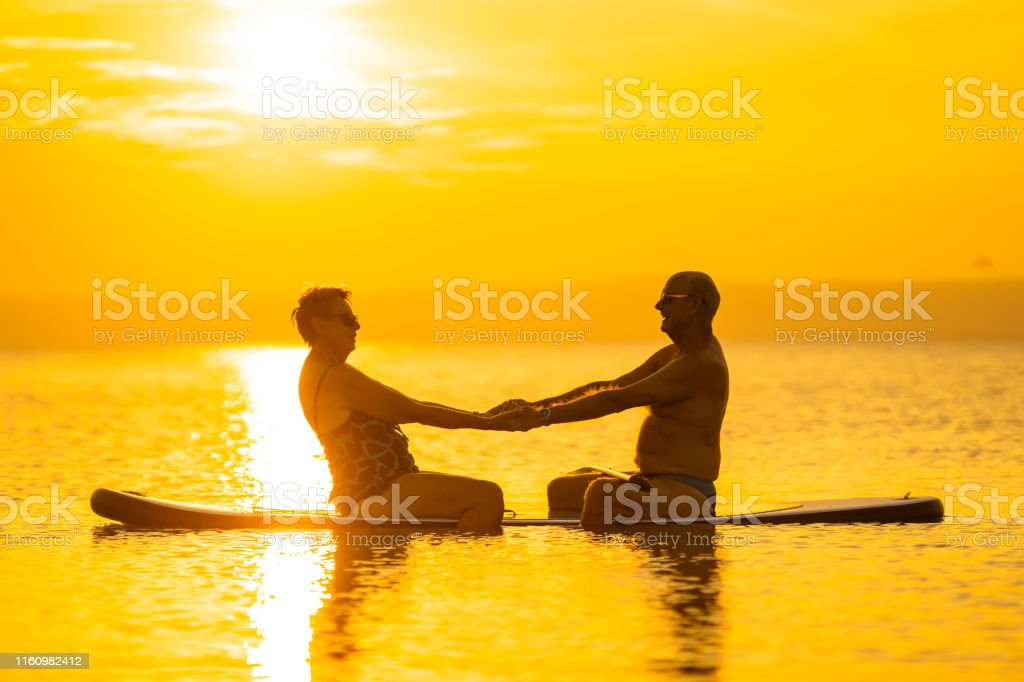senior couple 70 and 75 years old sitting on standup paddle board in...