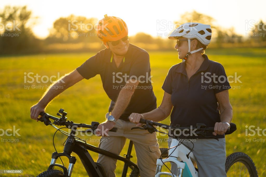 active senior couple with bike helmets and on their electric bicycles...
