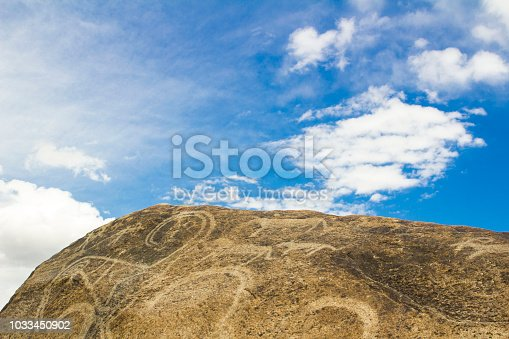 istock real petroglyphs on natural stone found in the steppe, on a blurred background of beautiful mountains 1033450902