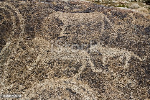 istock real petroglyphs on natural stone found in the steppe, on a blurred background of beautiful mountains 1033450970