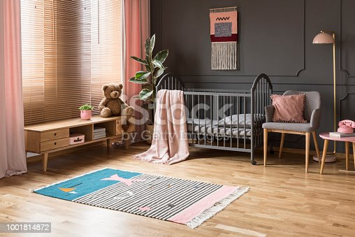 istock Real photo of a baby crib standing between a low cupboard and an armchair, lamp and stool in child's room interior with wooden floor and grey walls with moldings 1001814872