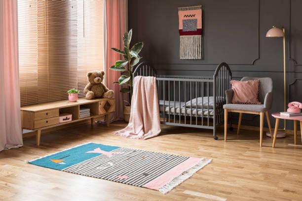 echtes foto von einem baby kinderbett stehen zwischen einem niedrigen schrank und sessel, lampe und stuhl des kindes innenraum mit holzboden und graue wände mit formteilen - mädchenraum vorhänge stock-fotos und bilder