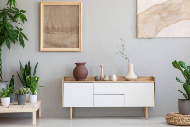 echtes foto von einem botanischen wohnzimmer interieur mit sackleinen-grafik auf dem grauen wand und weißen schrank umgeben von pflanzen - sideboard skandinavisch stock-fotos und bilder