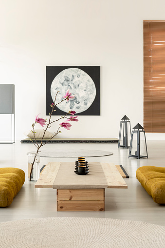 istock Real photo of a bright, oriental interior with a row of tea cups on a low, wooden table with yellow cushions on both sides and pink flowers decoration 1016348402
