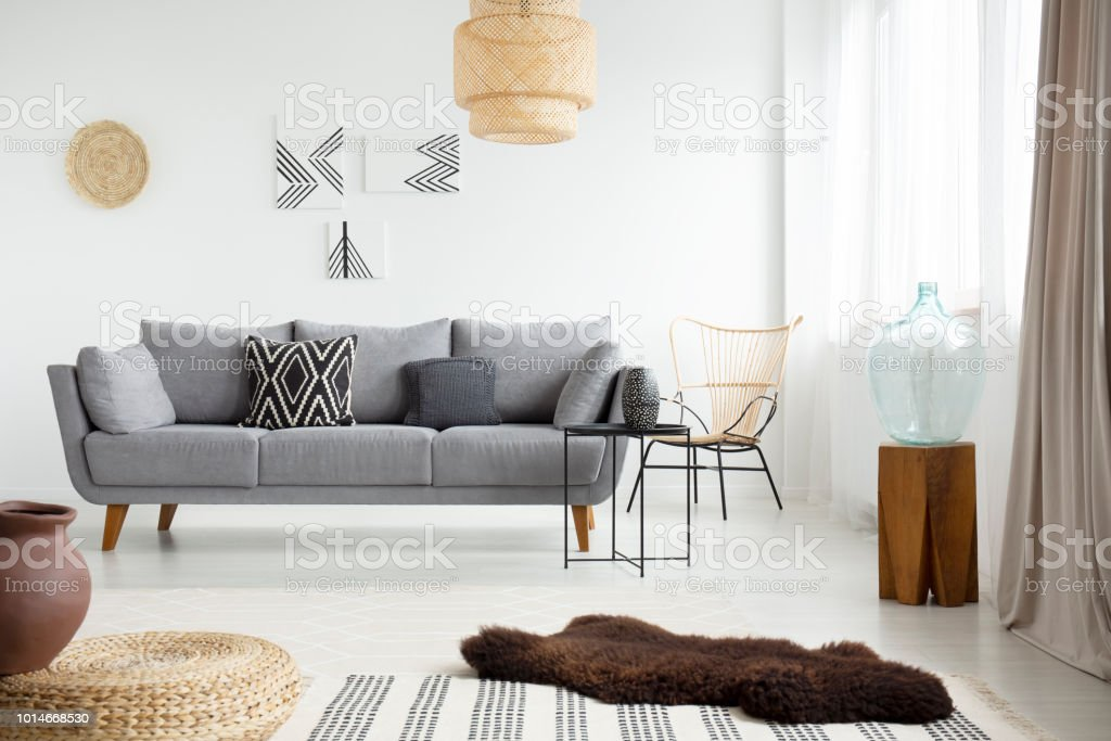 Real photo of a brown, fur rug lying on white floor in front of a gray couch with cushions in bright living room interior