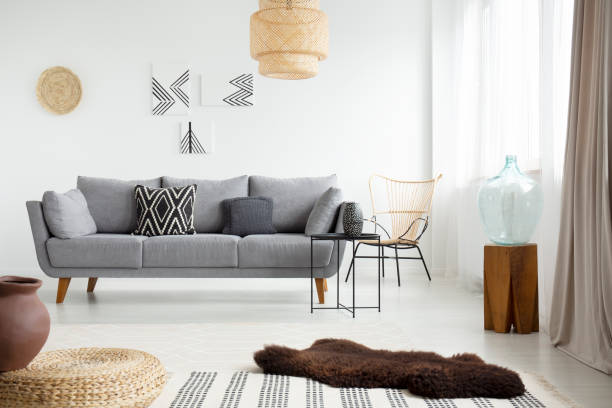 kahverengi, kürk halı gri bir kanepe önünde beyaz zemin aydınlık oturma odası iç yastıkları ile yatan gerçek fotoğraf - i̇skandinav kültürü stok fotoğraflar ve resimler