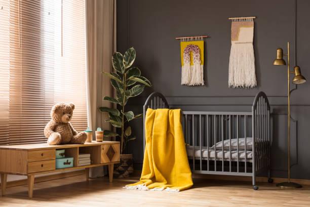 Echtes Foto ein Kinderbett mit einem gelben Decke stehen zwischen einem niedrigen Schrank mit einem Bären und einer Lampe in Baby-Innenraum – Foto