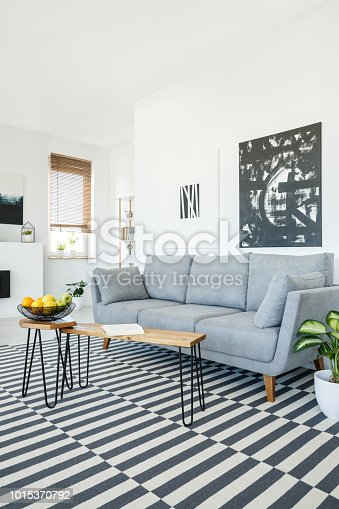 Real photo of a couch standing next to a wall with white and black paintings and behind a wooden table in cozy living room interior with striped rug