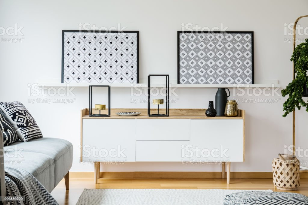 . Real Photo Of A Cupboard With Ornaments And Shelf With Posters Standing In  A Living Room Interior Next To A Couch And Plant Stock Photo   Download