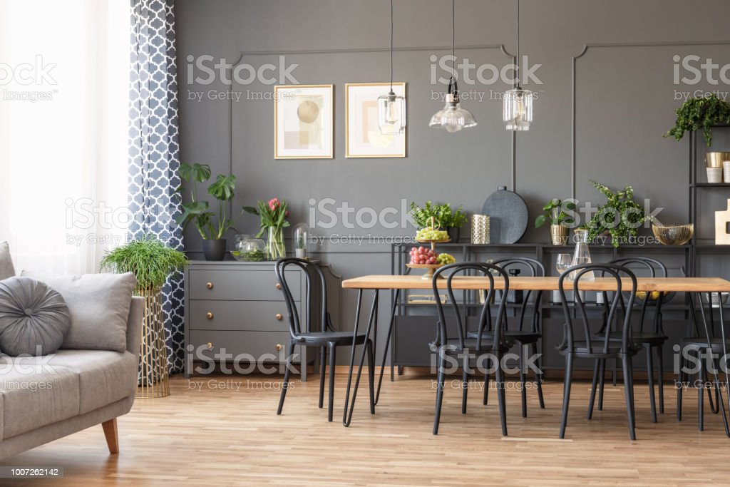 Real photo of a dark flat interior with gray couch, wooden dining table, black chairs and golden posters on the wall in open space living room stock photo