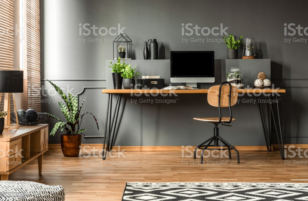 Real photo of a dark interior with wooden desk, chair and computer in the study space in the middle – zdjęcie