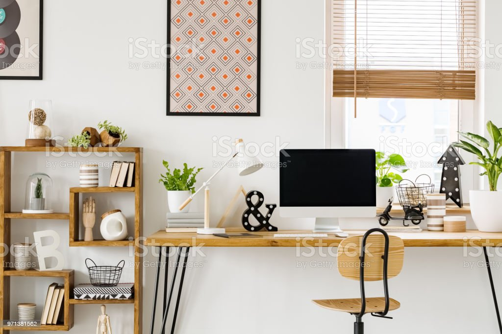 Real photo of a desk with a computer screen, lamp and ornaments...