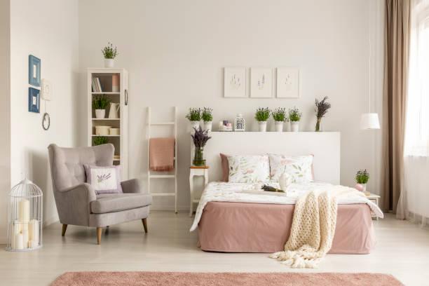 echtes foto von einem weiblichen schlafzimmer innenraum mit einem bequemen sessel, bett, pflanzen und regal - lila, grün, schlafzimmer stock-fotos und bilder