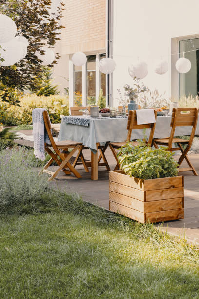 Real photo of a garden with a table, chairs, lamps and wooden box with plants stock photo