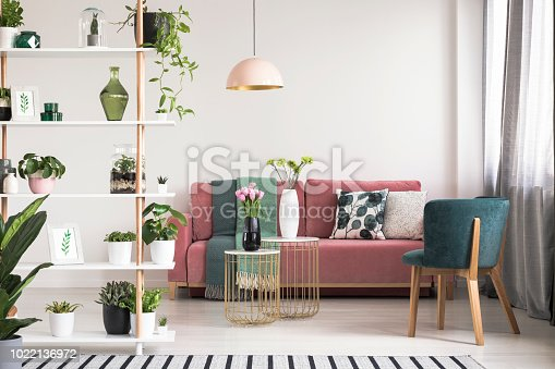 Real photo of a green armchair, pink couch, gold tables with flowers and wooden rack with plants in botanic living room interior