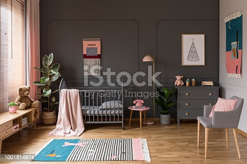 istock Real photo of a grey crib standing next to a pink stool, a lamp and cupboard in grey baby room interior also with armchair, rug and posters 1001814874
