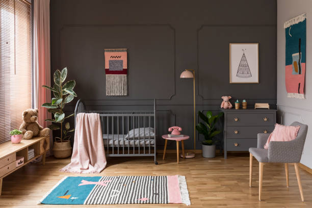Real photo of a grey crib standing next to a pink stool, a lamp and cupboard in grey baby room interior also with armchair, rug and posters stock photo
