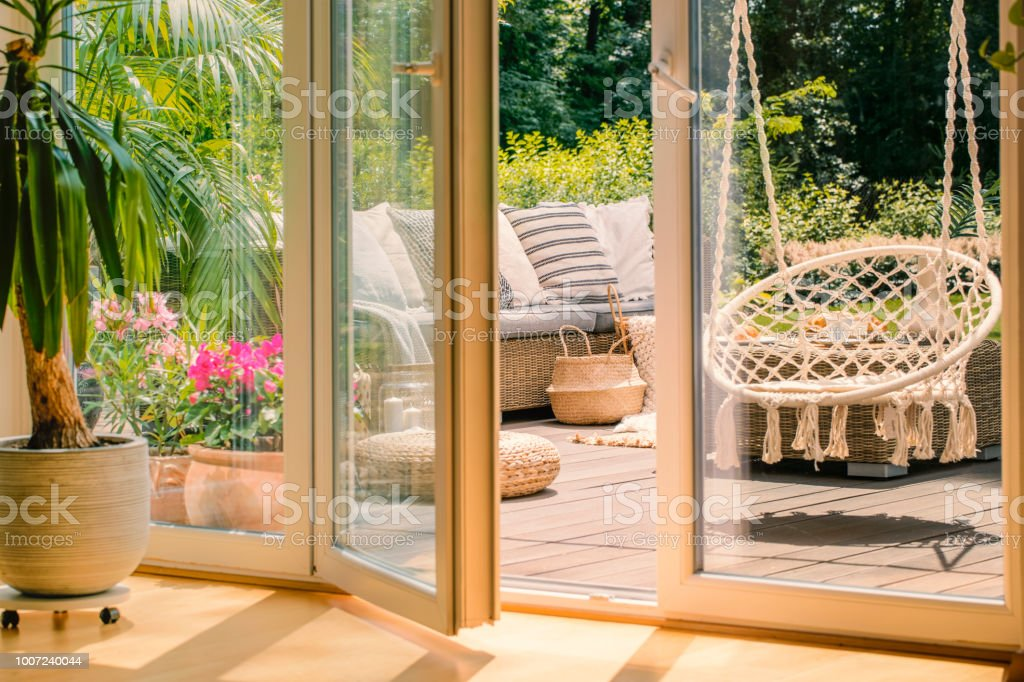 Real photo of a hanging armchair and a rattan sofa with cushions on a wooden patio behind the door stock photo