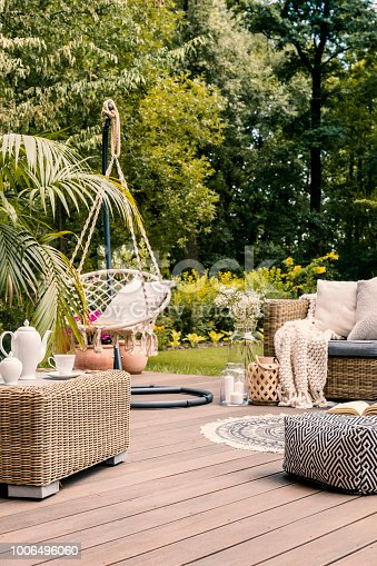 istock Real photo of a hanging chair and rattan furniture on a wooden terrace of a summer house 1006496060