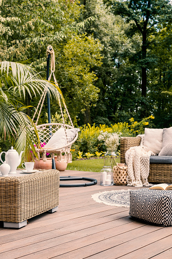 Real photo of a hanging chair and rattan furniture on a wooden terrace of a summer house
