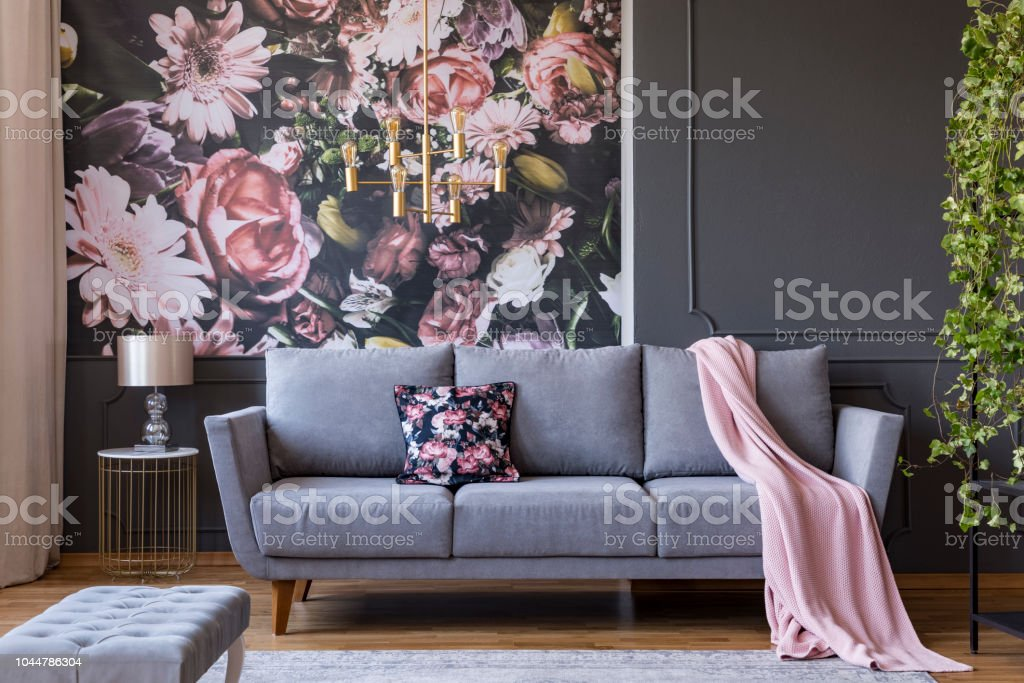Real photo of a living room interior with a sofa, pillow, blanket and flowers on wallpaper – zdjęcie