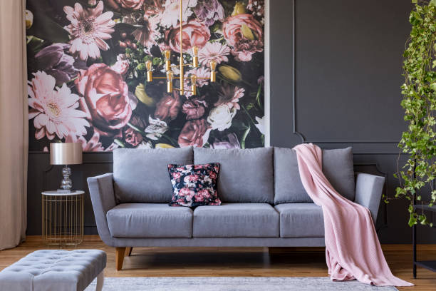 Real photo of a living room interior with a sofa, pillow, blanket and flowers on wallpaper stock photo